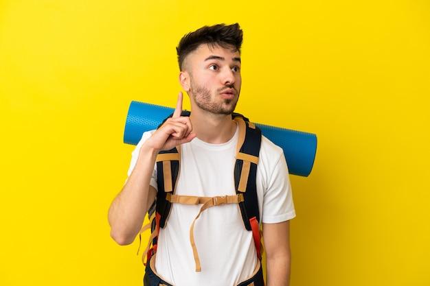 Jovem alpinista homem caucasiano com uma grande mochila isolada em um fundo amarelo pensando em uma ideia apontando o dedo para cima