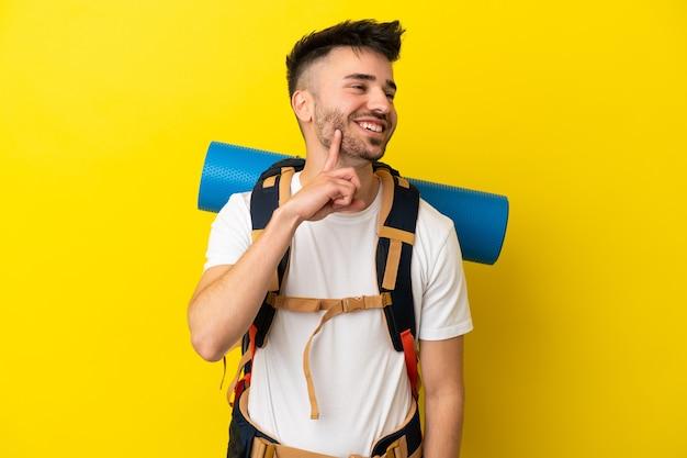 Jovem alpinista homem caucasiano com uma grande mochila isolada em um fundo amarelo pensando uma ideia enquanto olha para cima