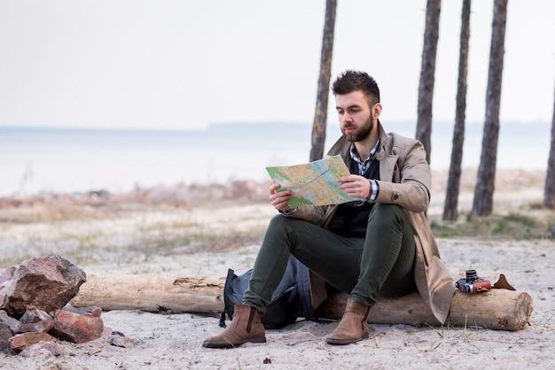 Jovem alpinista masculina sentado na praia sobre o log olhando mapa