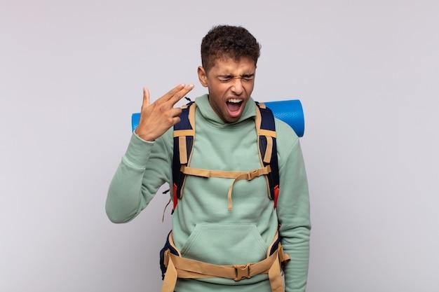 Jovem alpinista parecendo infeliz e estressado, gesto suicida fazendo sinal de arma com a mão