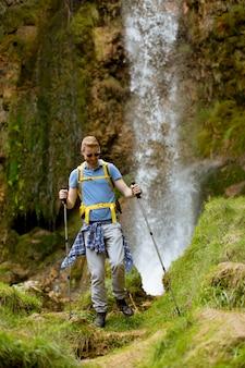 Jovem alpinista parou ao lado de uma cachoeira de montanha para descansar