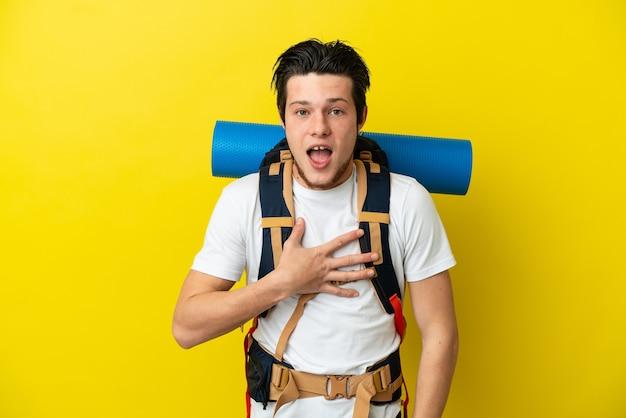 Jovem alpinista russo com uma mochila grande isolada em um fundo amarelo surpreso e chocado ao olhar para a direita