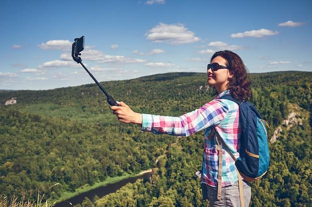 Jovem alpinista tirando foto com telefone inteligente no pico da montanha