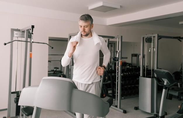 Jovem alto com roupas esportivas, correndo em uma esteira no ginásio. treinamento cardíaco.