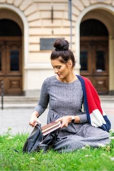 Jovem aluna adulta coloca livros na mochila, sentada na grama perto do prédio da universidade