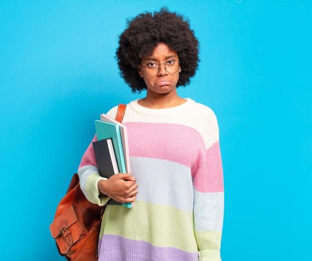 Jovem aluna afro se sentindo triste e chorona com um olhar infeliz, chorando com uma atitude negativa e frustrada