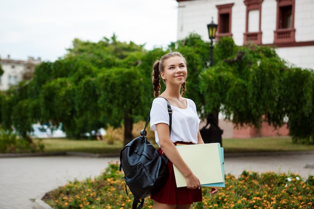 Jovem aluna alegre linda sorrindo, segurando pastas ao ar livre.