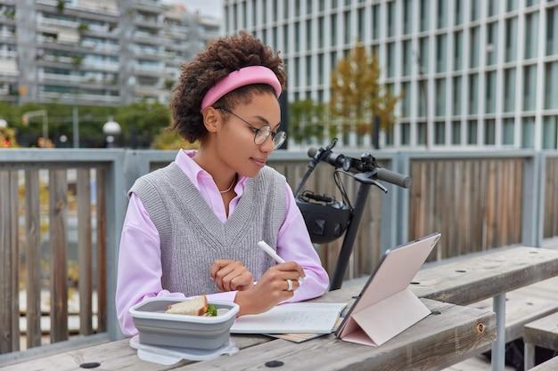 Jovem aluna assiste a um webinar ou vídeo tutorial concentrado na tela do tablet escreve anotações no bloco de notas, informações do projeto posa do lado de fora contra uma atmosfera aconchegante cria um plano