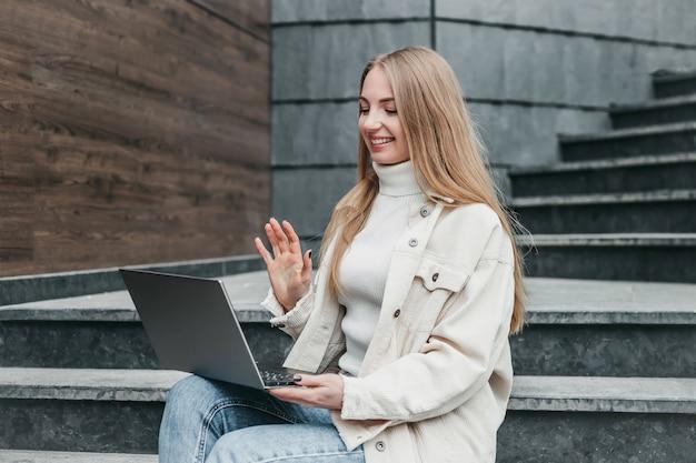 Jovem aluna branca sentada na escada perto de sua faculdade com um laptop, sorrindo e fazendo uma videochamada