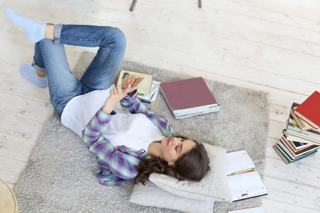 Jovem aluna checando as redes sociais antes de voltar a estudar, deitada no chão contra o aconchegante interior doméstico, cercada por uma pilha de livros.