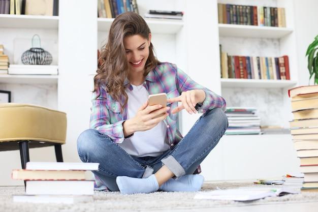 Jovem aluna checando as redes sociais antes de voltar a estudar, sentada no chão contra o aconchegante interior doméstico, cercada por uma pilha de livros.
