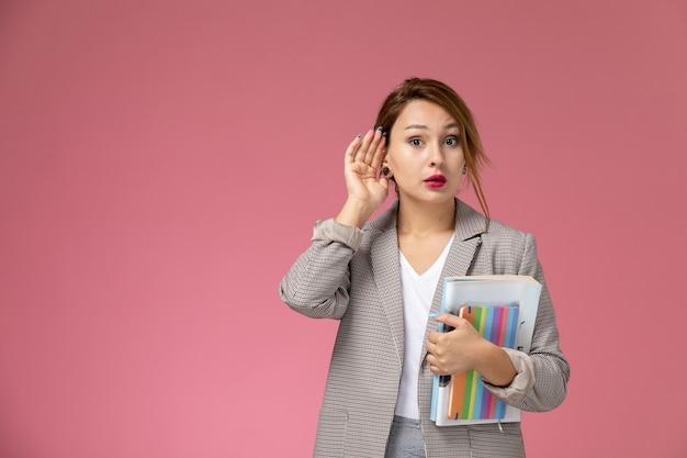Jovem aluna com casaco cinza posando segurando livros, tentando ouvir sobre o fundo rosa, aulas de faculdade universitária