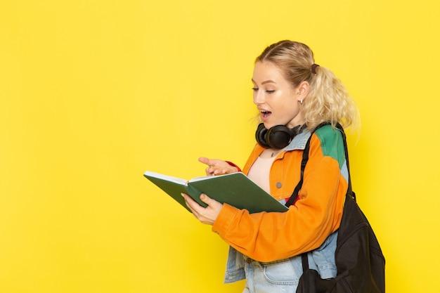 Jovem aluna com roupas modernas segurando a leitura do caderno em amarelo