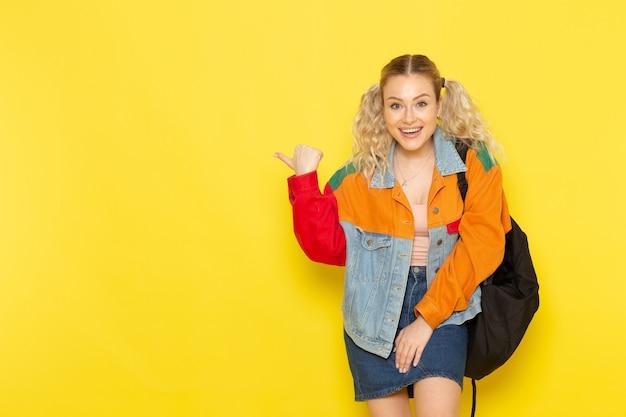 Jovem aluna com roupas modernas simplesmente posando com um sorriso apontando no amarelo