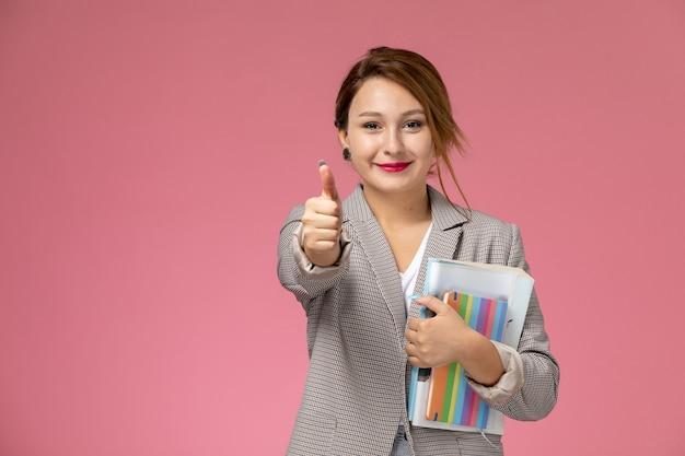 Jovem aluna de casaco cinza posando de frente para os livros, mostrando como um cartaz com um sorriso no fundo rosa