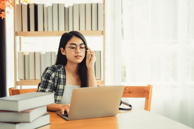 Jovem aluna em camisa xadrez, sentada à mesa usando o laptop enquanto estudava.