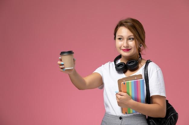 Jovem aluna em camiseta branca com bolsa e fones de ouvido posando e sorrindo segurando café no fundo rosa lição