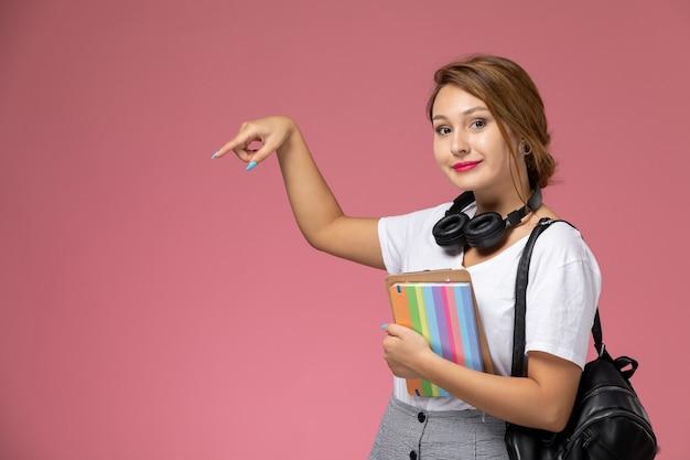 Jovem aluna em camiseta branca sorrindo segurando cadernos no fundo rosa