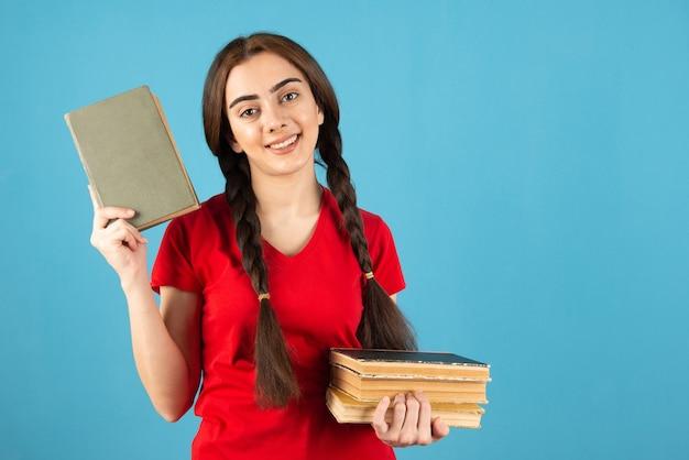 Jovem aluna em t-shirt vermelha com livros em pé na parede azul.