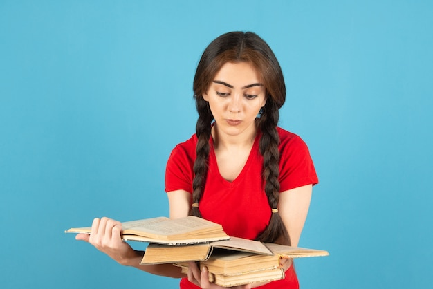 Jovem aluna em t-shirt vermelha, lendo um livro na parede azul.