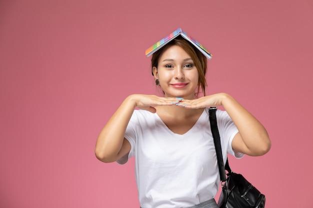 Jovem aluna em uma camiseta branca com um caderno e uma bolsa posando com uma expressão fofa no fundo rosa.