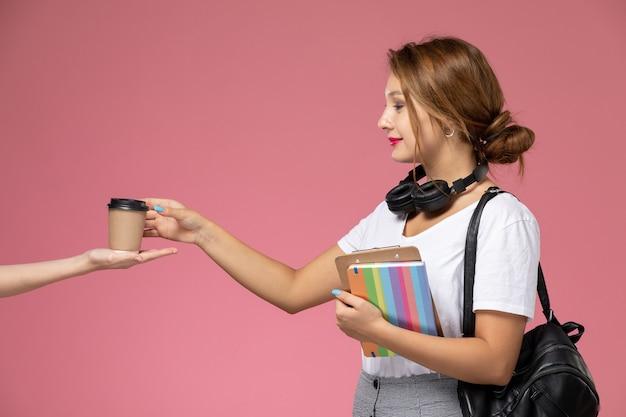 Jovem aluna em uma camiseta branca com um caderno e uma bolsa posando e pegando a xícara de café no fundo rosa.