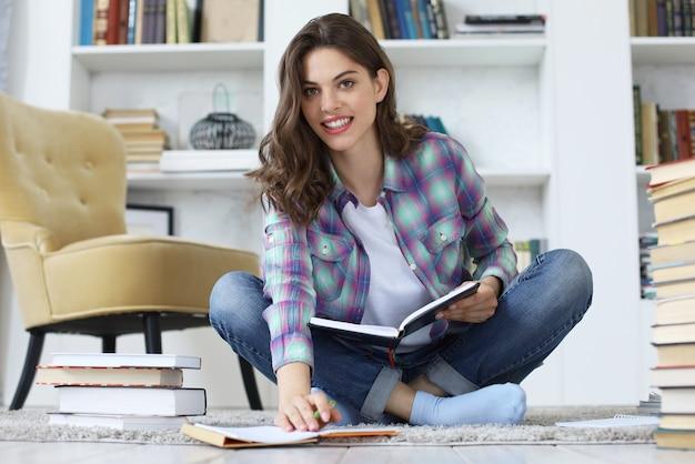 Jovem aluna estudando em casa, escrevendo um artigo para publicação, sentada no chão contra o aconchegante interior doméstico, cercada por uma pilha de livros.