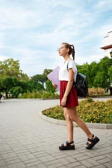 Jovem aluna linda de óculos sorrindo, segurando pastas ao ar livre.
