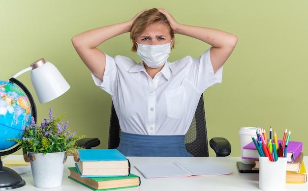 Jovem aluna loira carrancuda usando máscara protetora, sentada na mesa com ferramentas escolares, mantendo as mãos na cabeça, olhando para a câmera isolada na parede verde oliva