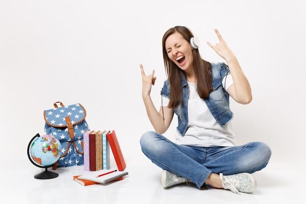 Jovem aluna maluca com fones de ouvido ouvindo música mostrando uma placa de rock-n-roll gritando perto da mochila de livros escolares do globo