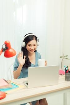 Jovem aluna navegando notebook sentar desktop vídeo chamada ouvir aula online webinar conferência educação distância social quarentena dentro de casa