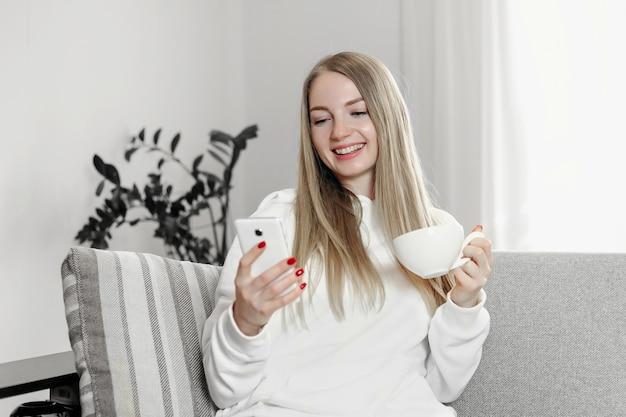 Jovem aluna olha para a tela de um telefone celular, faz uma videoconferência e sorri enquanto está sentada no sofá em frente à janela