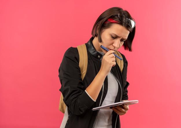 Jovem aluna pensativa usando óculos na cabeça e na mochila segurando uma caneta e um bloco de notas, olhando para o bloco de notas tocando seus lábios com o dedo isolado na parede rosa