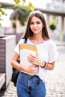 Jovem aluna talentosa vestida com roupas casuais, andando pela cidade. mulher morena atraente, aproveitando o tempo livre ao ar livre