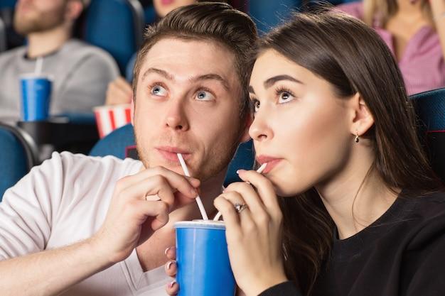 Jovem amando beber a mesma bebida junto com dois canudos assistindo filmes no cinema local