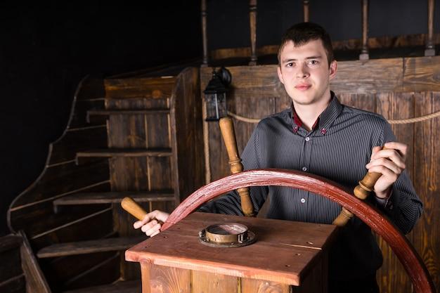 Jovem ambicioso homem de negócios vestindo camisa listrada e parado no leme do navio, dirigindo o barco com uma roda de madeira e olhando para a câmera