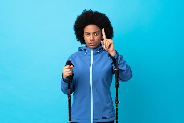 Jovem americana africana com pólos de mochila e trekking isolados no azul, contando um com expressão séria
