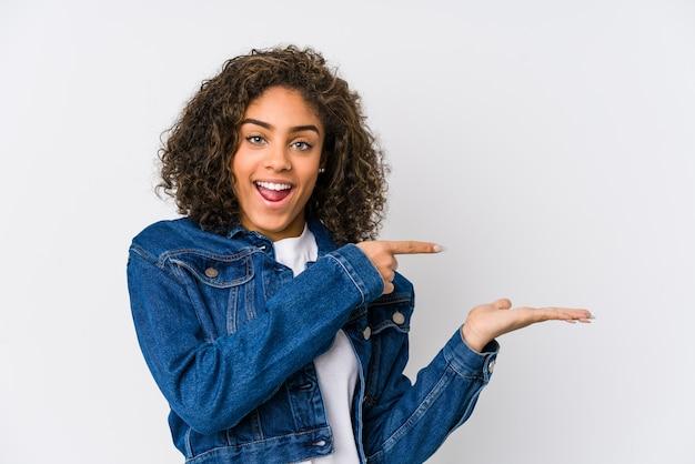 Jovem americana africano animado segurando um espaço de cópia na palma da mão.