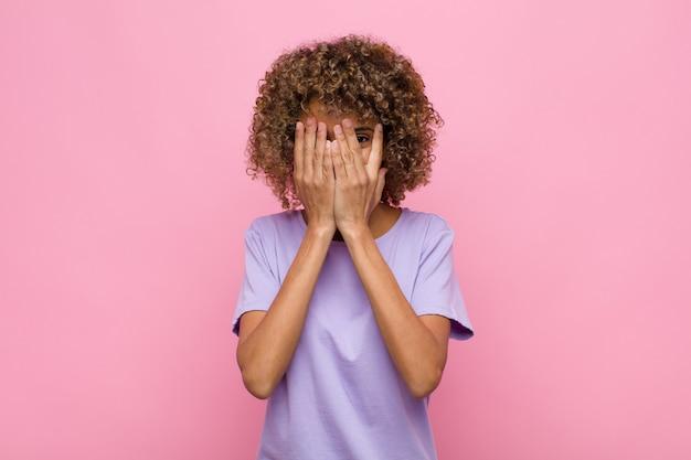 Jovem americana africano, cobrindo o rosto com as mãos, espreitar entre os dedos com expressão de surpresa e olhando para o lado contra a parede rosa