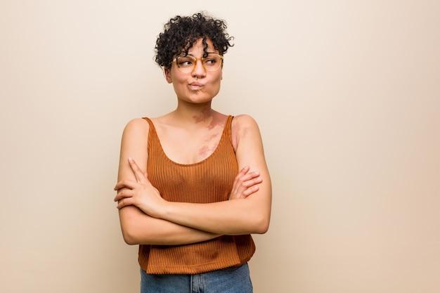 Jovem americana africano com marca de nascença de pele carrancuda rosto em descontentamento, mantém os braços cruzados.