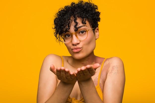 Jovem americana africano com marca de nascimento de pele, dobrar os lábios e segurando as palmas das mãos para enviar beijo de ar.