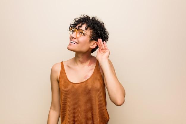 Jovem americana africano com marca de nascimento de pele tentando ouvir uma fofoca.