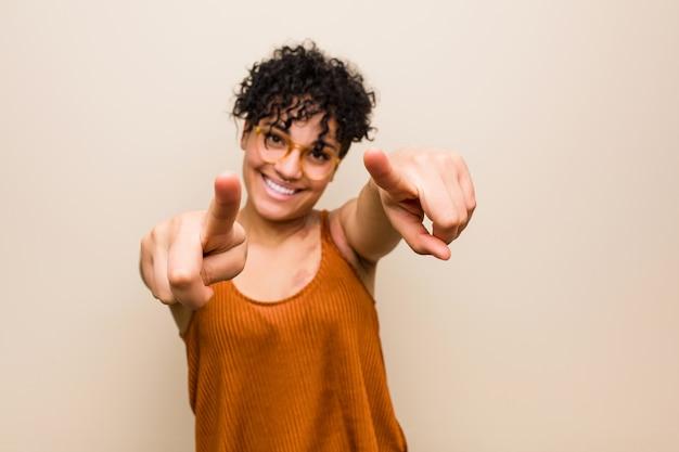 Jovem americana africano com sorrisos alegres de marca de nascimento de pele apontando para a frente.