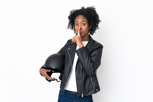Jovem americana africano com um capacete de moto isolado na parede branca, fazendo o gesto de silêncio