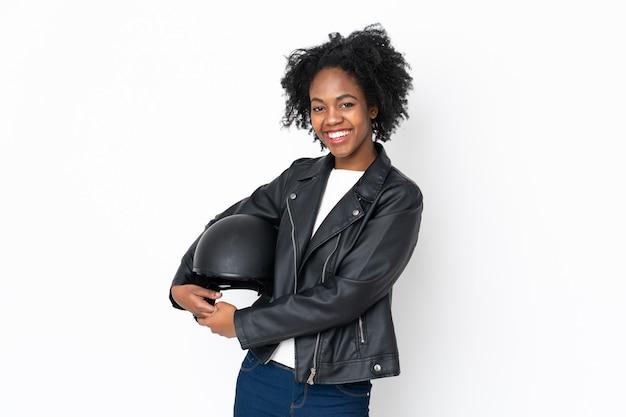 Jovem americana africano com um capacete de moto isolado na parede branca rindo