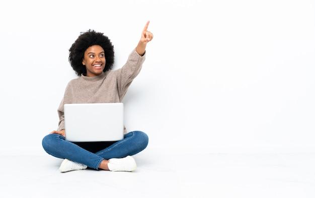 Jovem americana africano com um laptop sentado no chão apontando para fora