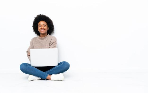 Jovem americana africano com um laptop sentado no chão com os braços cruzados e feliz
