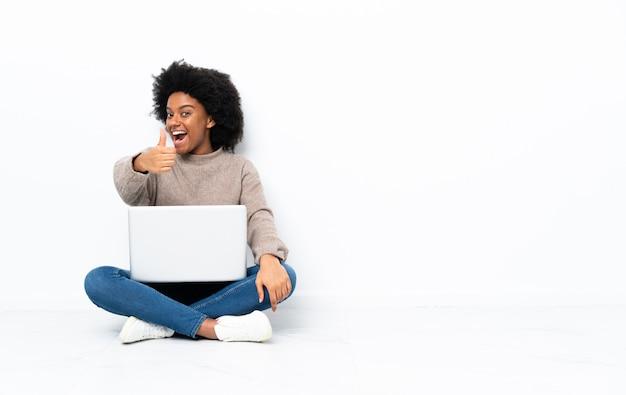 Jovem americana africano com um laptop sentado no chão com os polegares para cima, porque algo de bom aconteceu