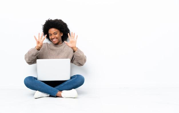 Jovem americana africano com um laptop sentado no chão, contando nove com os dedos