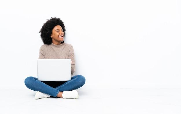Jovem americana africano com um laptop sentado no chão feliz e sorridente